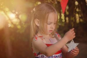 little girl holding a star decoration by Samantha Brown Photography