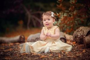 Little girl sitting on autumn leaves by Samantha Brown Photography