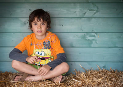 boy sitting on hay in a barn by samantha brown photography
