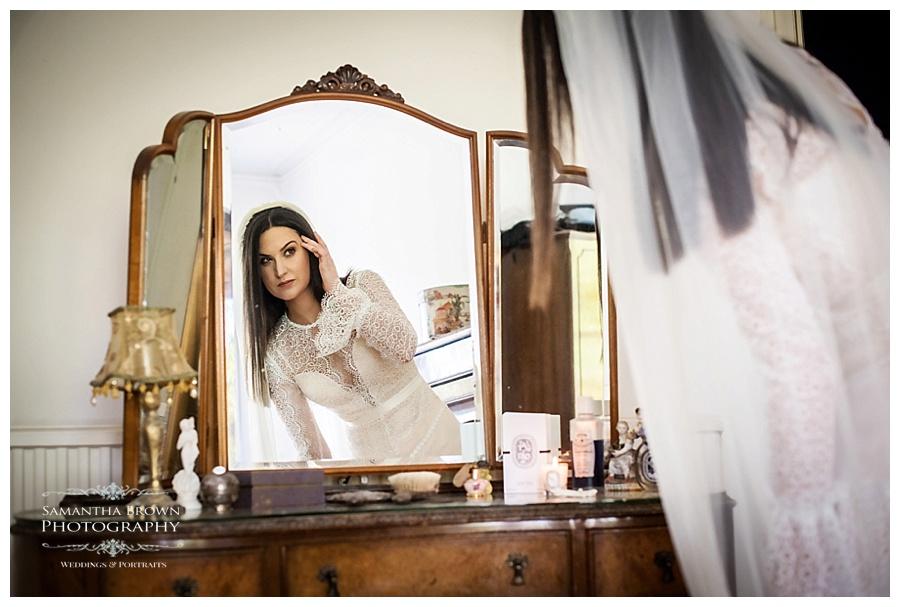 Bride looking in the mirror before wedding